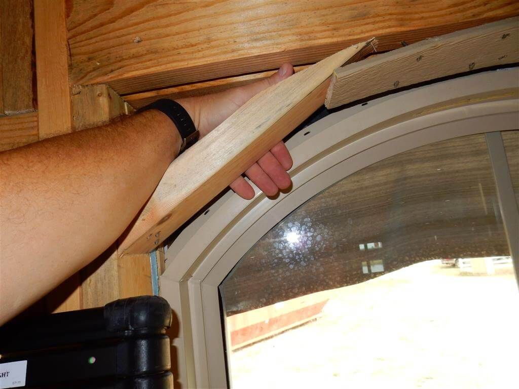 Arched window with the arch/flange not supported, not fastened, not caulked, not overlapping sheathing and not integrated into the water resistive barrier/drainage plane.