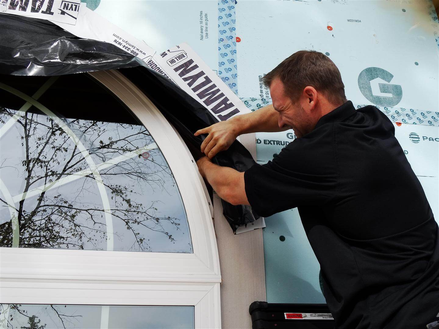 Arched window with the arch/flange not supported, not fastened, not caulked, not overlapping sheathing and not integrated into the water resistive barrier/drainage plane
