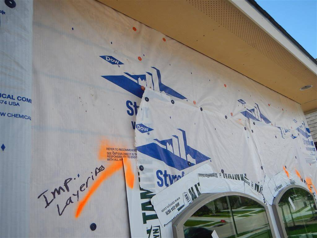 This window is not properly integrated into the water-resistive barrier/drainage plane. The the housewrap above the window is not layered in shingle fashion. Water can enter behind the added flap above the window. This was a failed attempt at correcting the initial problem of the top flap of the housewrap being inside rather than outside of the window flange. Clearly the installer is incompetent going 0 for 2 attempts.